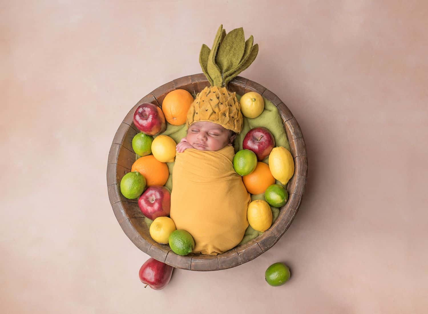 The best newborn photography props include fun themes like this fruit bowl concept. A newborn baby is wrapped in yellow and swaddled in a wooden bowl. The baby wears a felt pineapple hat and is surrounded by lemons, limes, oranges, and apples.