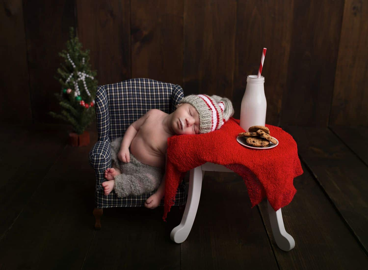 A tiny baby is posed with newborn photography props: a tiny chair and table topped with a red cloth, a bottle of milk, and a plate of miniature cookies.