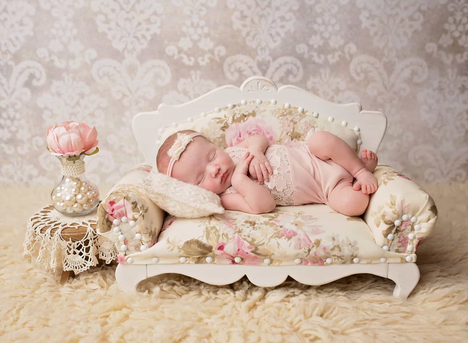 The best newborn photography props include luxurious items like this tiny wooden sofa upholstered with floral fabric and finished with pearl beads. In this photo, a baby girl lies on her side in a pink onesie. The sofa sits on a cream shag rug, and damask wallpaper hands in the background.