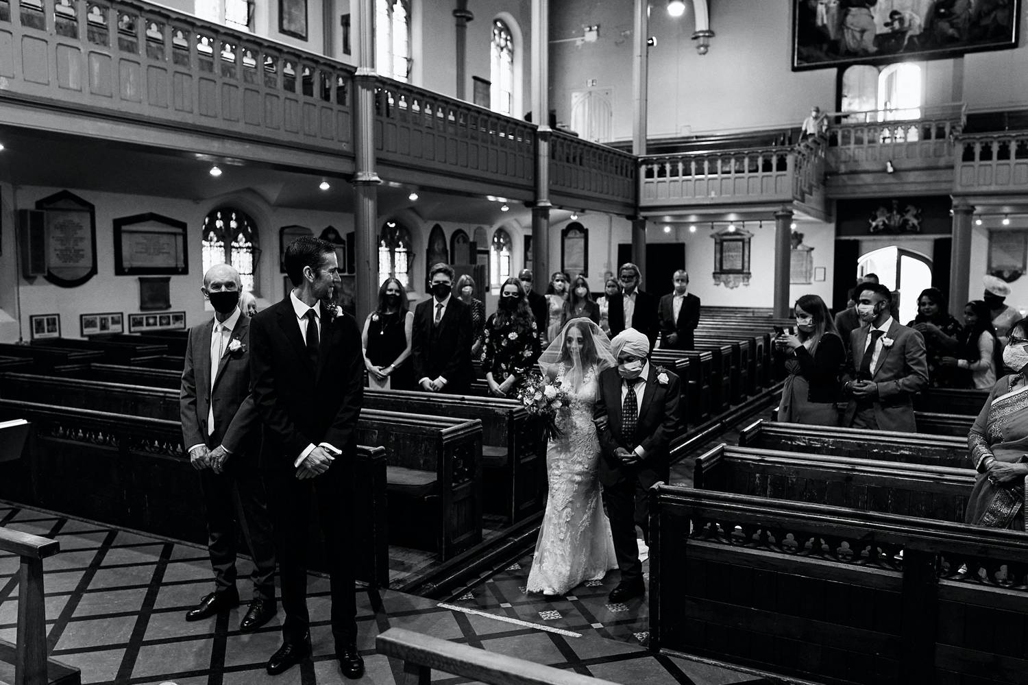 2020 Photographers are Resilient: a black and white photograph of a bride entering the church with her father, who wears a face mask.