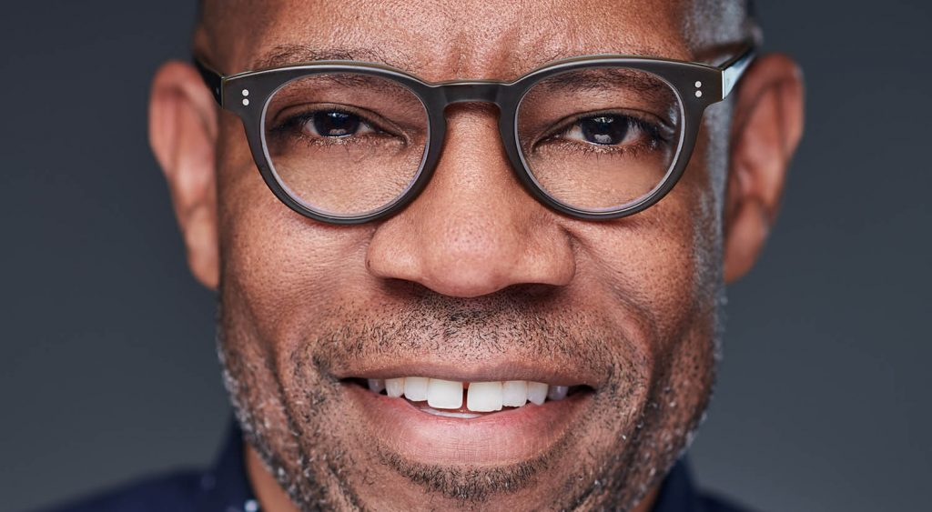 Headshot of photographer Damien Carter wearing modern, thick-framed glasses in a close-up portrait against a dark gray background for episode XX of Find Your Focus with ShootProof