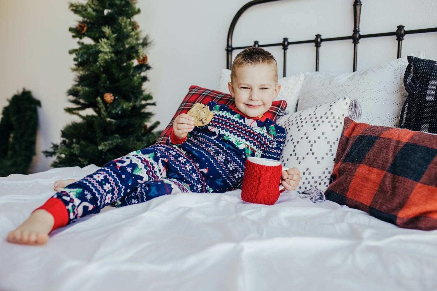 In this photo by Logan Fahey, a little boy wearing Christmas pajamas reclines on a white bed with a cookie and a red mug of hot cocoa in his hands. Christmas Mini Session: Ideas Families will ADORE!