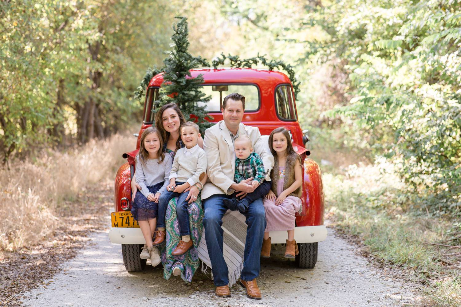 In this photo by Rebecca Rice, a mom, dad, and four young kids sit on the back of a red pickup truck that's draped with garland and decorated with a small Christmas tree. Christmas Mini Sessions: Ideas Families will ADORE!