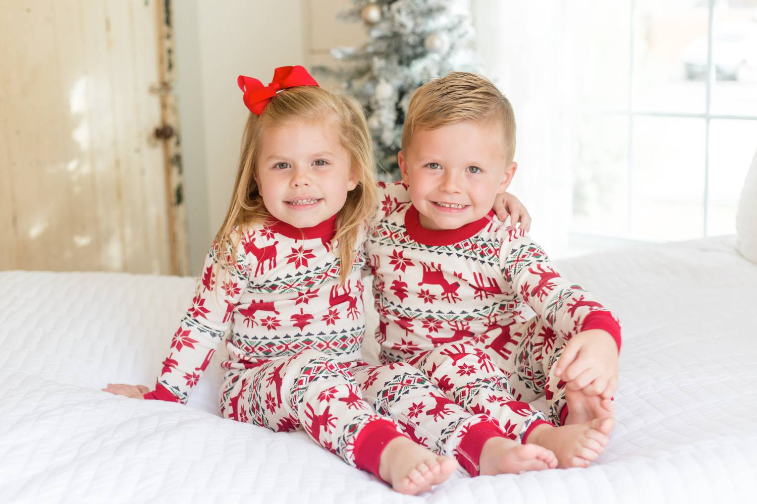 In this photo by Rebecca Rice, toddler twins wearing Christmas pajamas sit on a white-draped bed with their arms around each other as they smile at the camera. Christmas Mini Session: Ideas Families will ADORE!