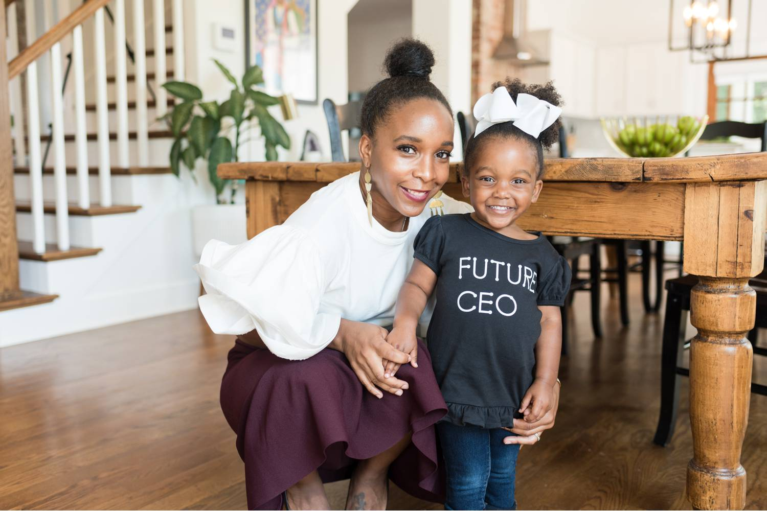 """By Mandy Liz: A CEO poses in her dining room with her young daughter whose shirt reads """"Future CEO."""" Great client feedback begins with confident leaders!"""