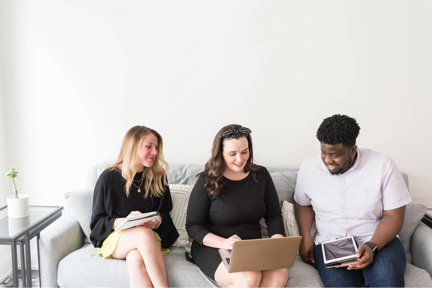 By Mandy Liz: Three adults sit on a sofa smiling and reviewing client feedback on a laptop.
