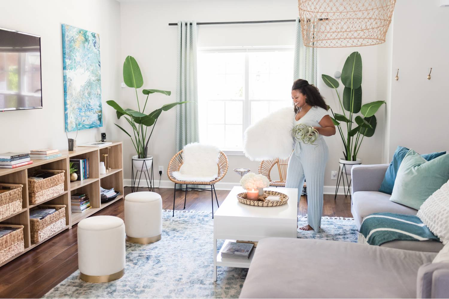 By Mandy Liz: An interior designer places decor in a brightly lit room while considering the phenomenal client feedback she'll certainly receive.