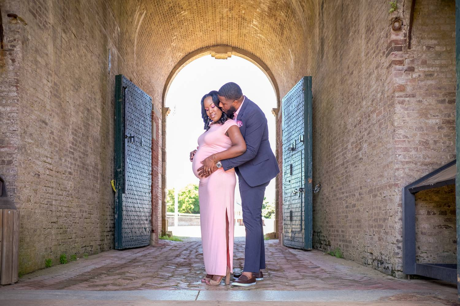 A pregnant woman in a fitted pink dress is embraced from behind by a man in a blue suit. They stand in the archway of an outdoor portico framed by old wooden doors.