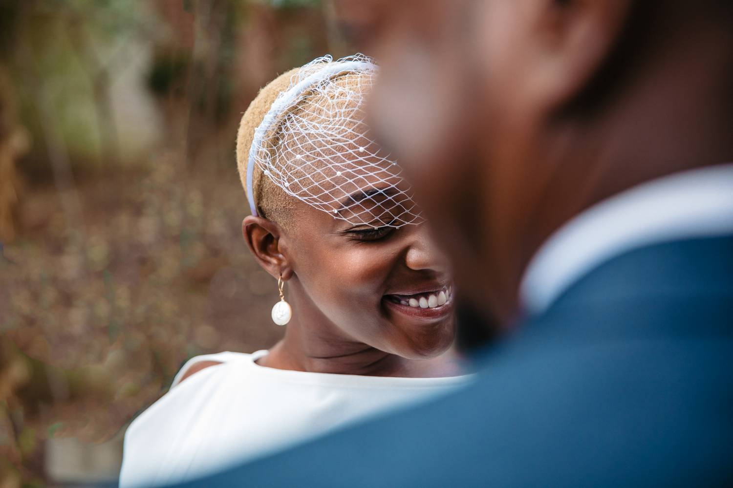 A Black bride wearing an art deco blusher smiles as she's photographed over the shoulder of her husband-to-be