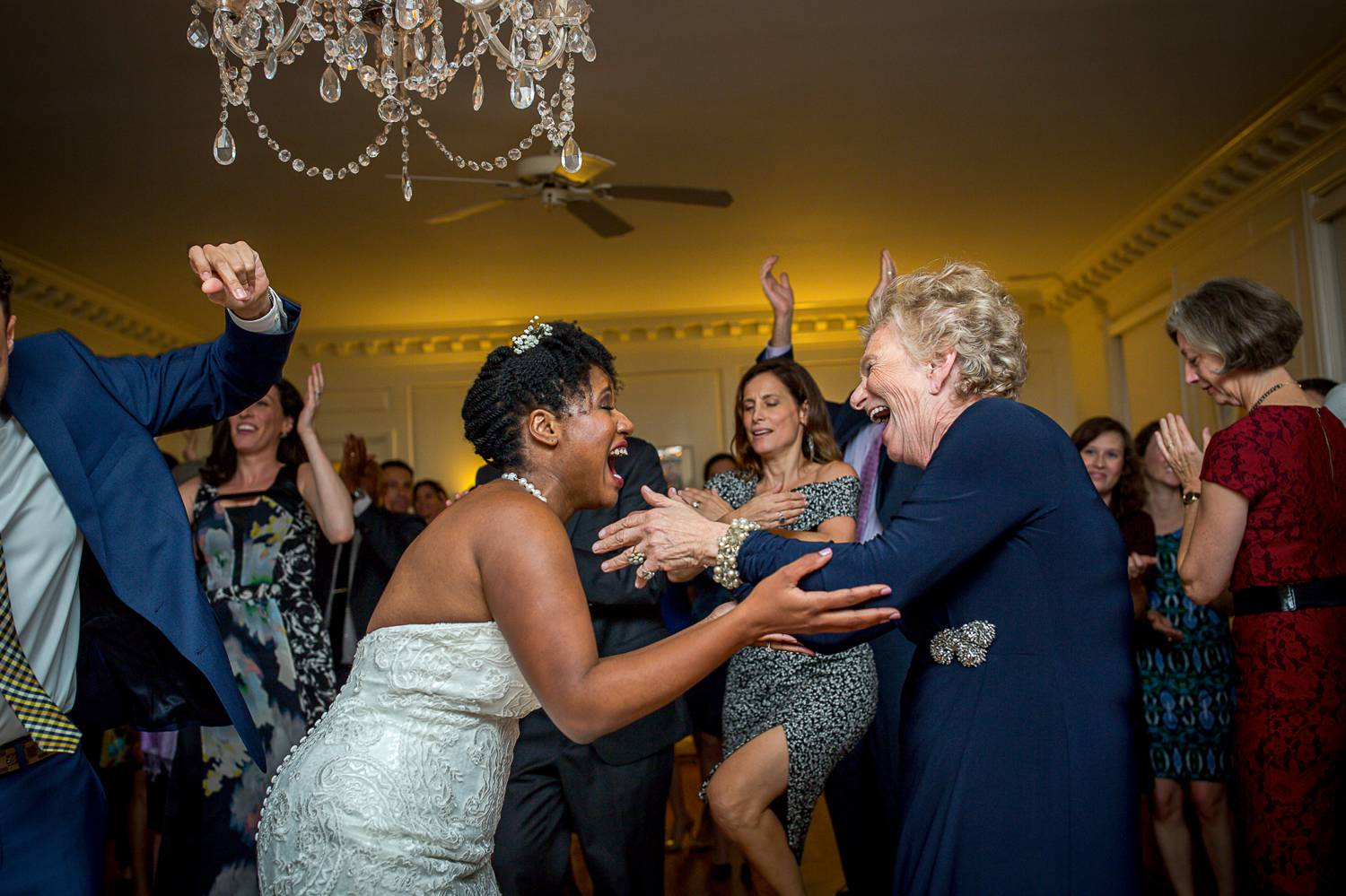 A Black bride and a white grandmother smile joyously as they reach toward eachother across a crowded dance floor