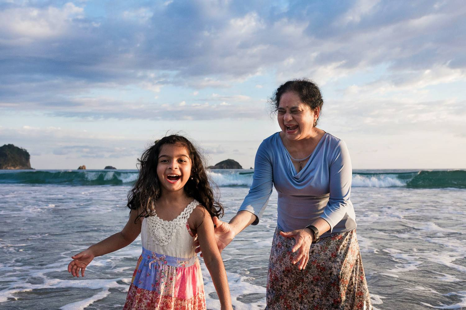 Client Experience: Kevin Heslin's photograph of an Indian woman and her granddaughter playing on a beach at sunset.