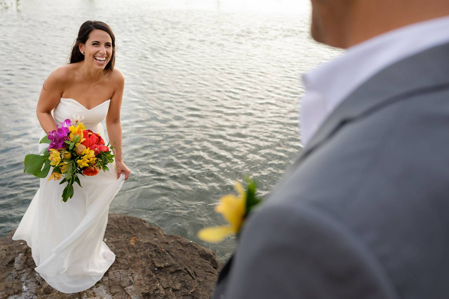 Client Experience: A photo by Kevin Heslin depicts a bride as she approaches her groom during their first look on a beach.