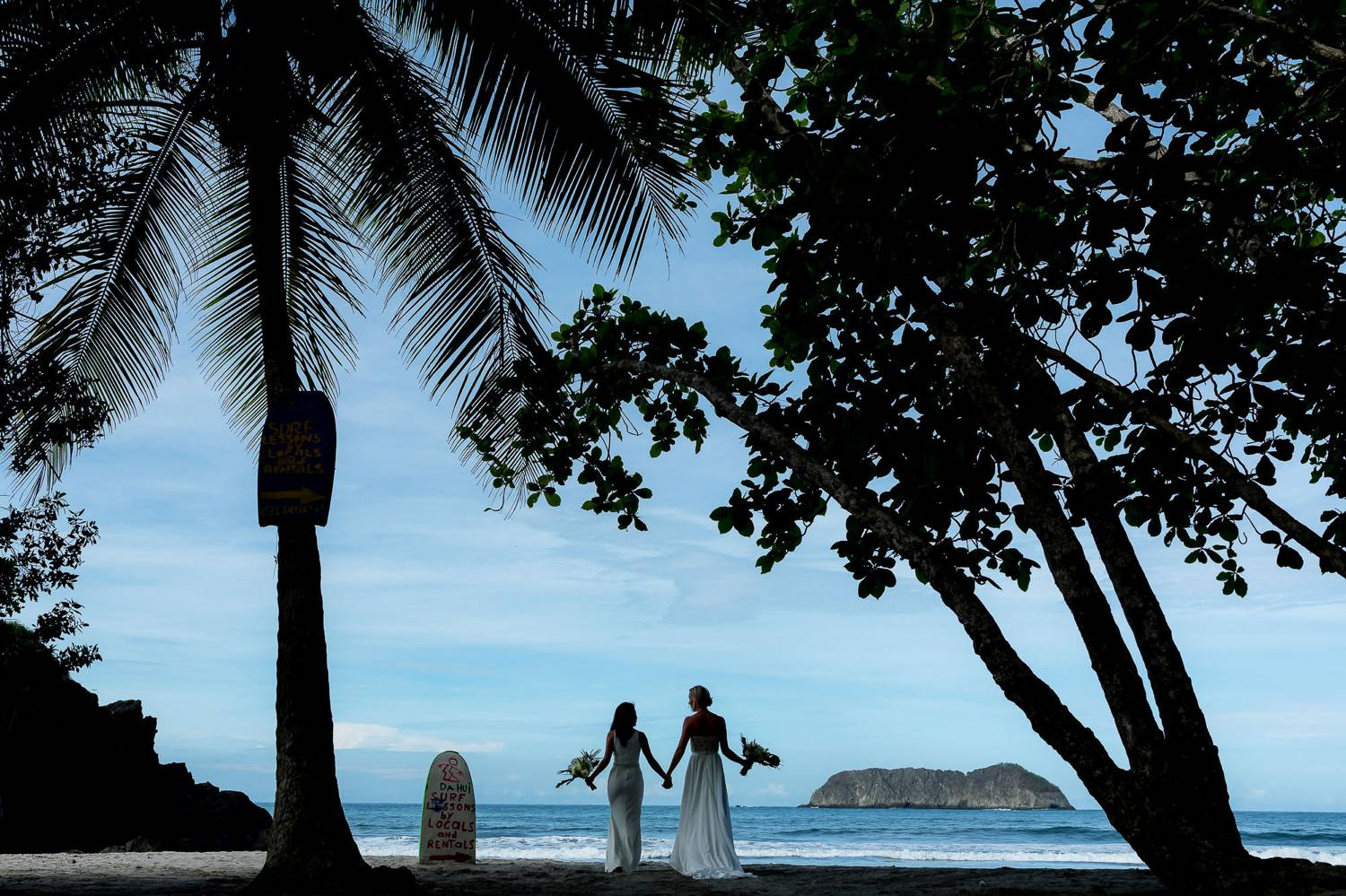 Client Experience: A photograph by Kevin Heslin depicts the sillhouettes of newlywed brides through palm trees as they walk along a beach at sunset.