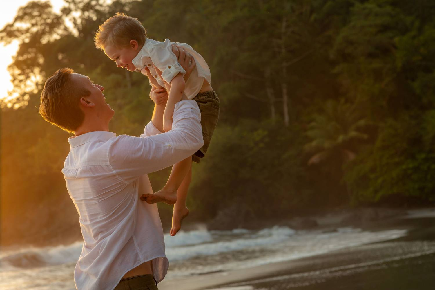 Client Experience: A photo by Kevin Heslin depicts a dad on a beach raising his child playfully toward the sky at sunset.