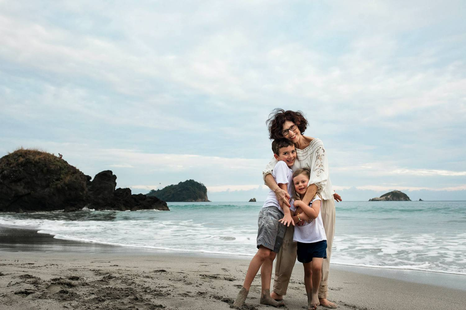A photo of Kevin Heslin depicts a curly-haired mom on a beach holding her sons.