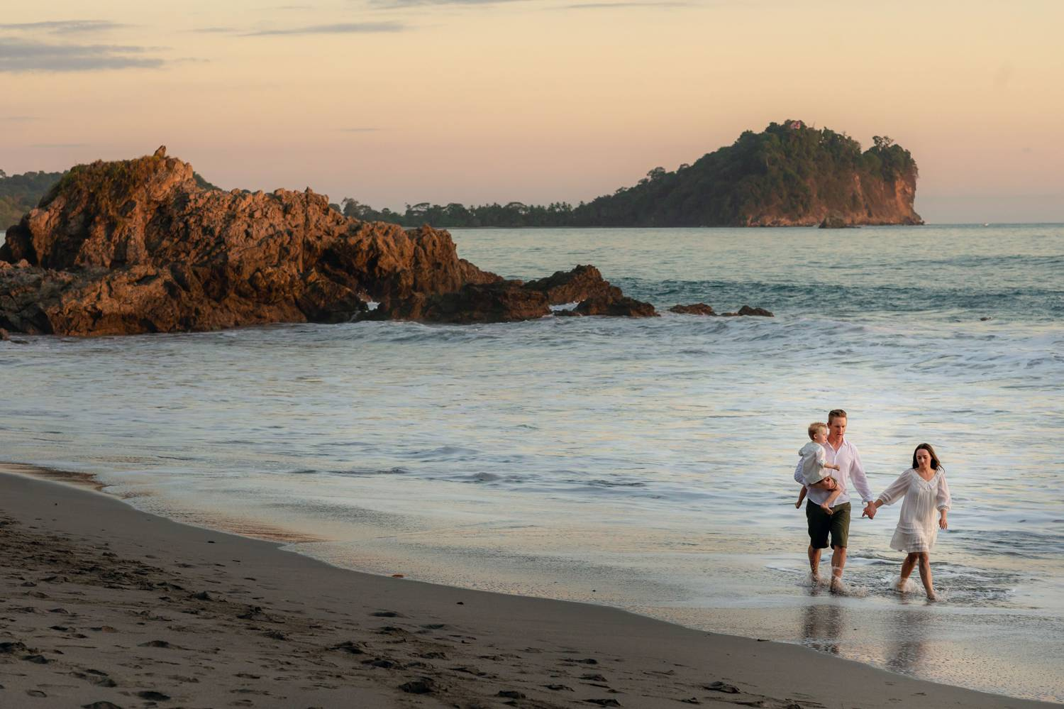 Client Experience: A photo by Kevin Heslin depicts a couple standing in the surf of a beach at sunset while holding their young child.