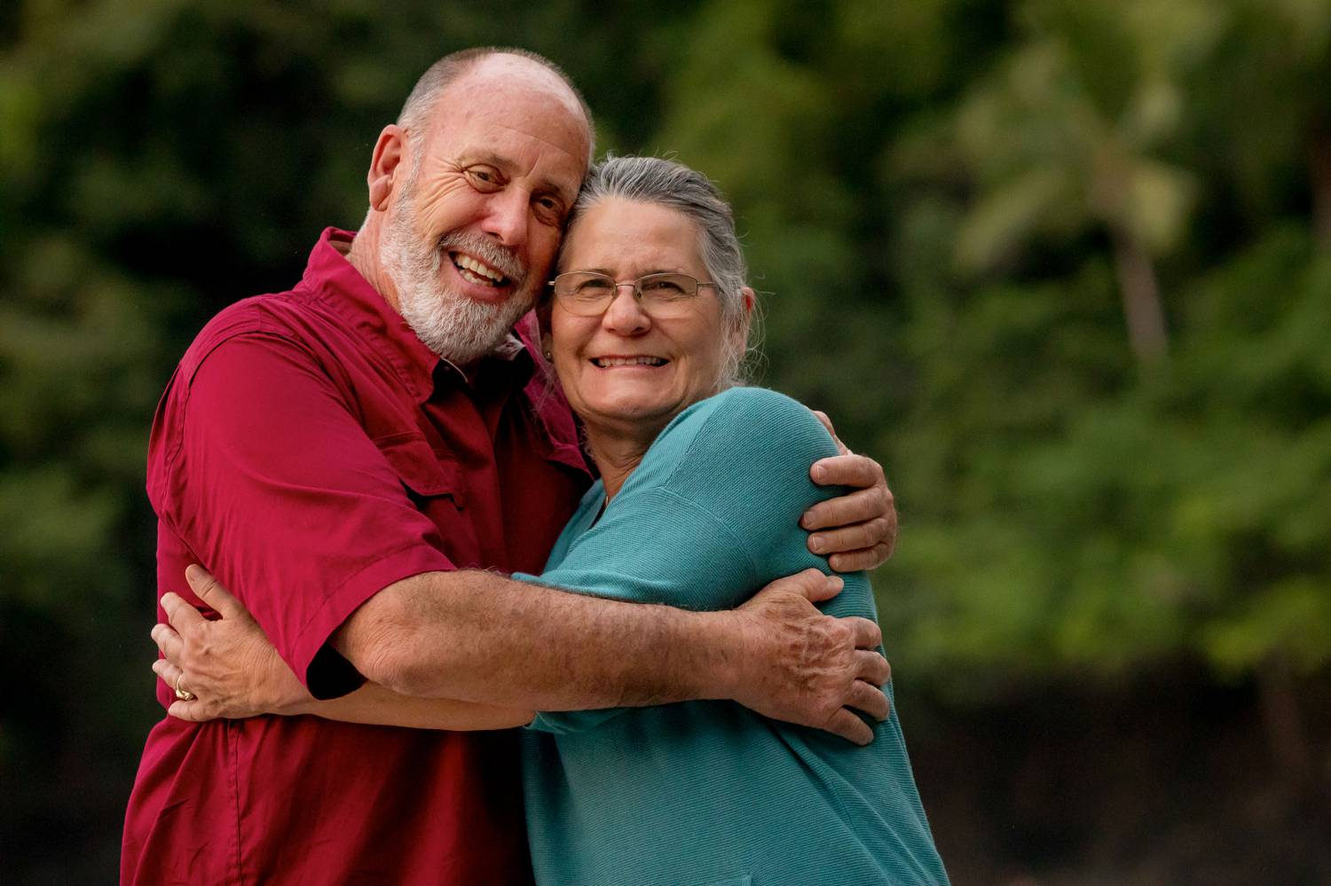 A photo by Kevin Heslin depicts a gray-bearded man with his arms wrapped around his silver-haired partner.