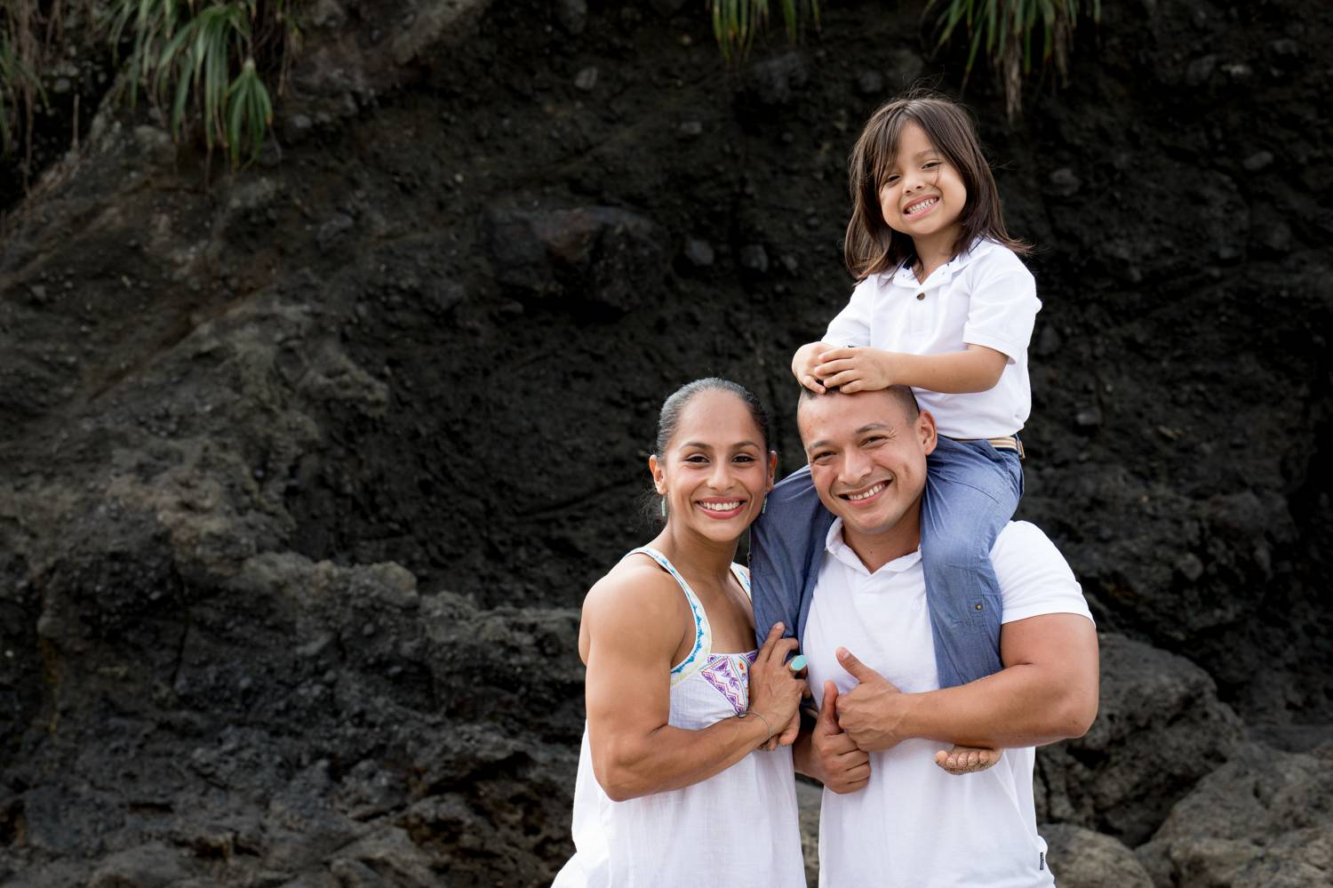 A photo by Kevin Heslin depicts two parents wearing white and posing with a smile as their child sits on the dad's shoulders.
