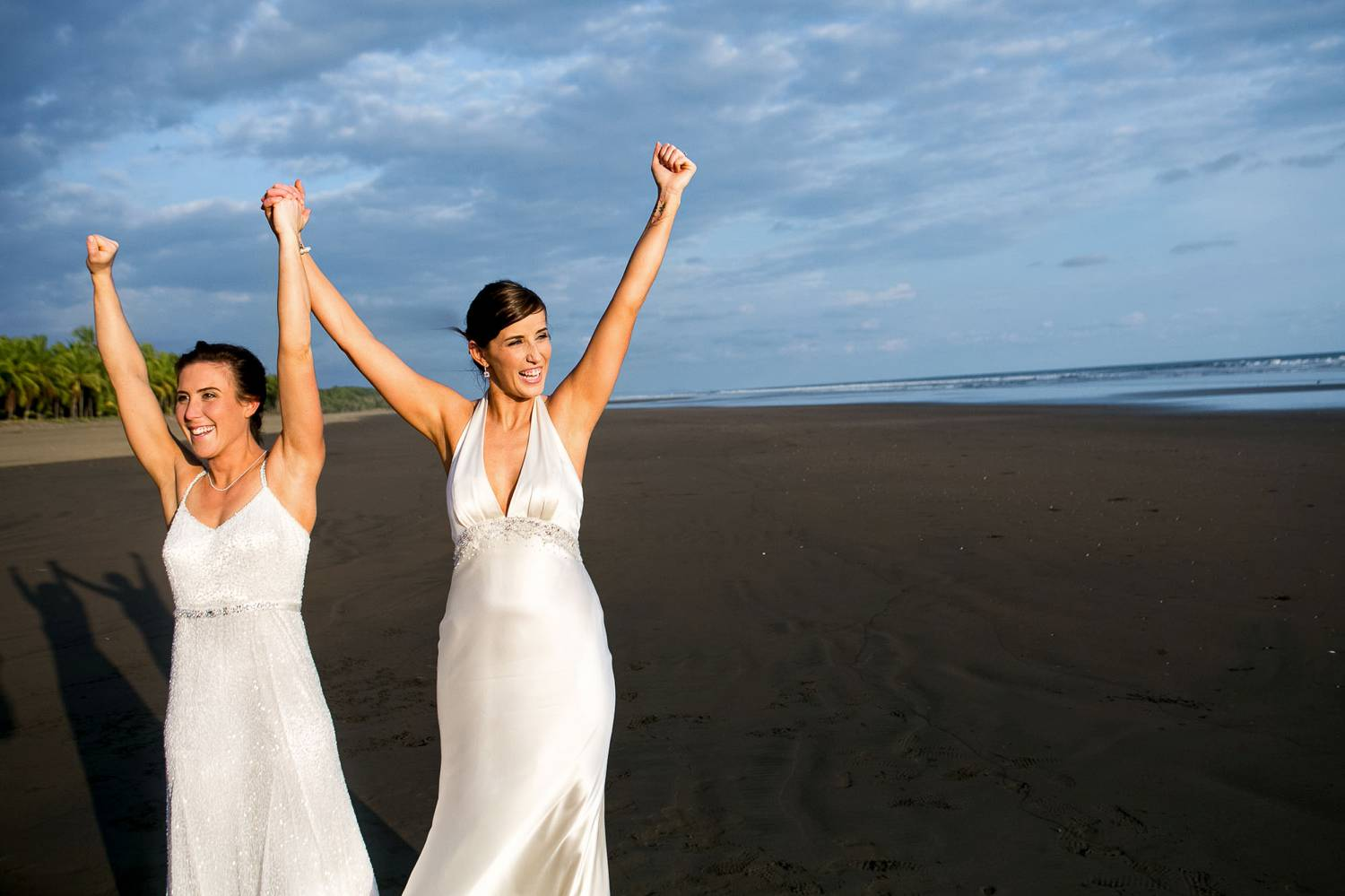 Client Experience: A wide-angle photo by Kevin Heslin depicts two brides in white silk dresses with their arms raised to the sky on the beach.