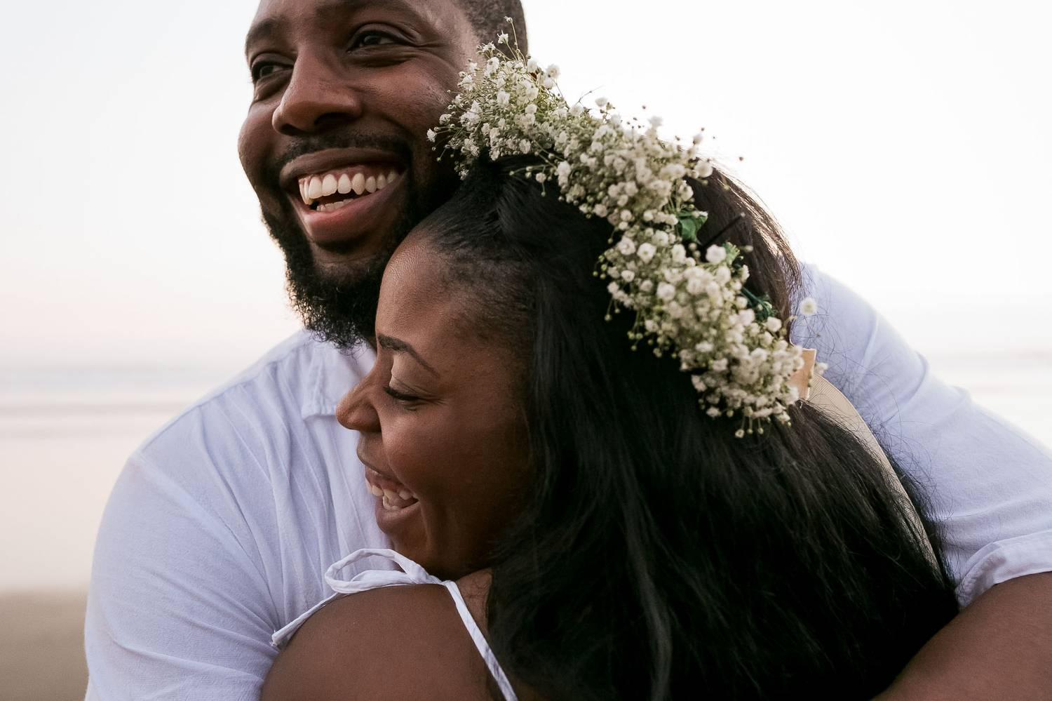 A close-up photo by Kevin Heslin depicts a Black bride and groom laughing and hugging on a beach.