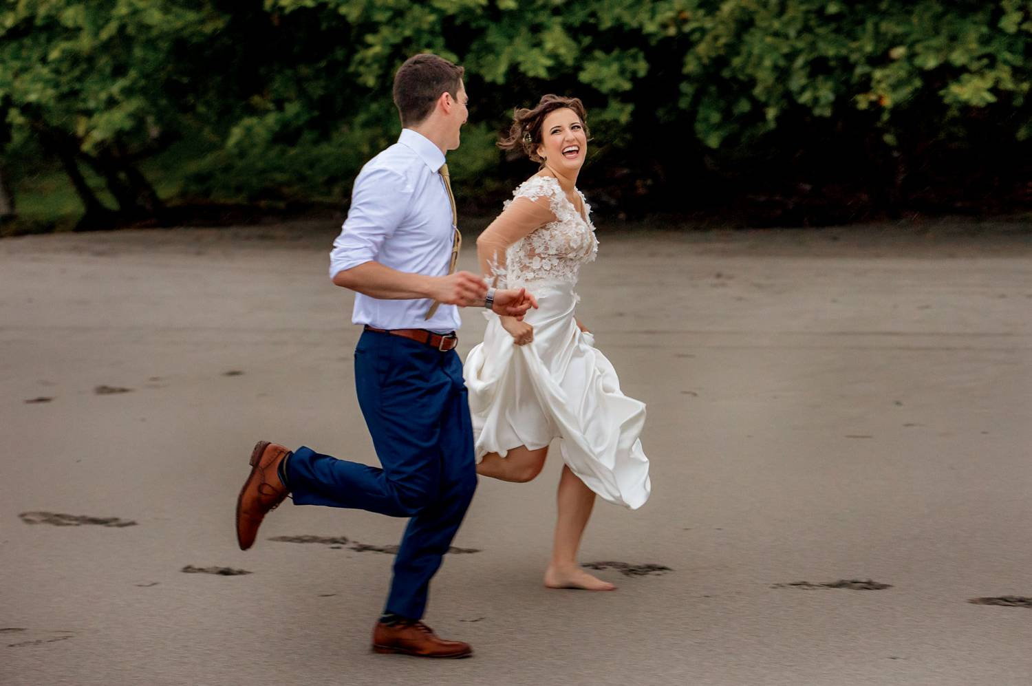 Client Experience: A photo by Kevin Heslin depicts a bride and groom running along a beach in their wedding clothes.